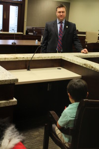 Therapy Dog Jerzy Girl sits in court with a young boy talking to District Attorney Matt Ballard